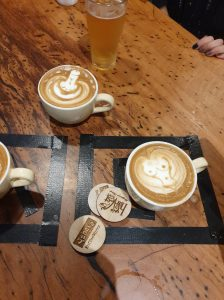 coffee coasters and cups of coffee with latte foam art