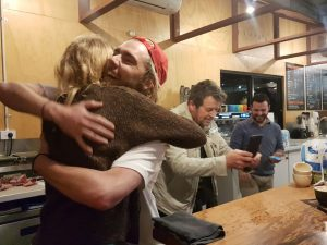 man and woman hugging after winning coffee latte art contest with friends taking photos of the coffee art