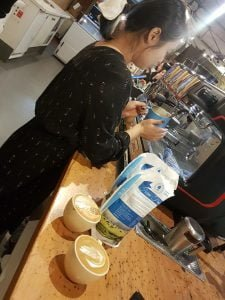 woman frothing milk to create cups of coffee with latte art