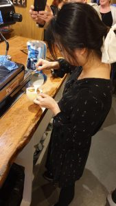 woman pouring foam to create cups of coffee with latte art