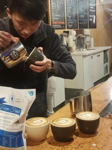man pouring foam to create cups of coffee with latte art