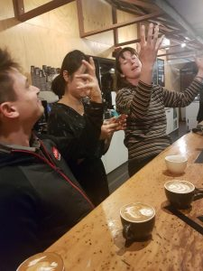 smiling men and women working on coffee latte art